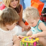 Tagesmutter spielt mit Kindern